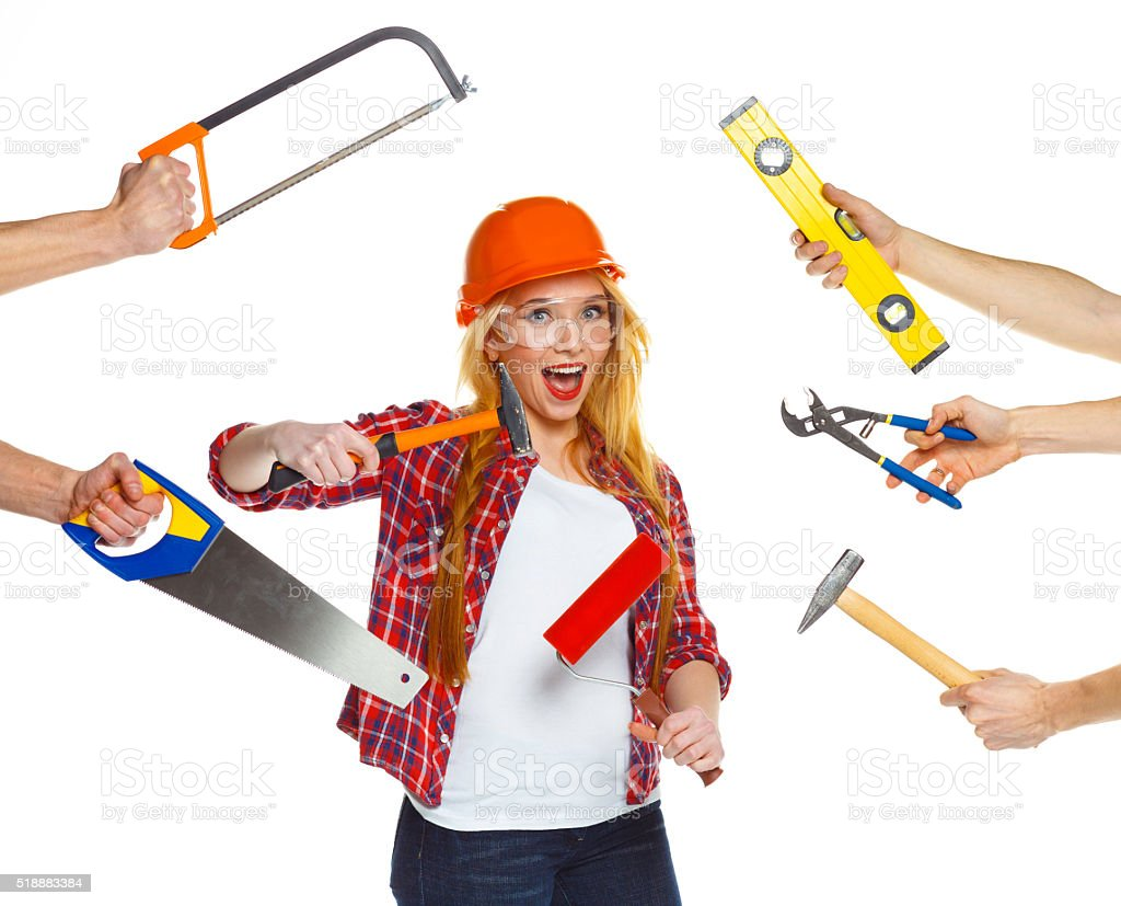 Funny girl in a helmet with different work tools stock photo