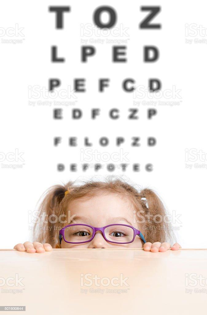 Funny girl in eyeglasses with eye chart stock photo