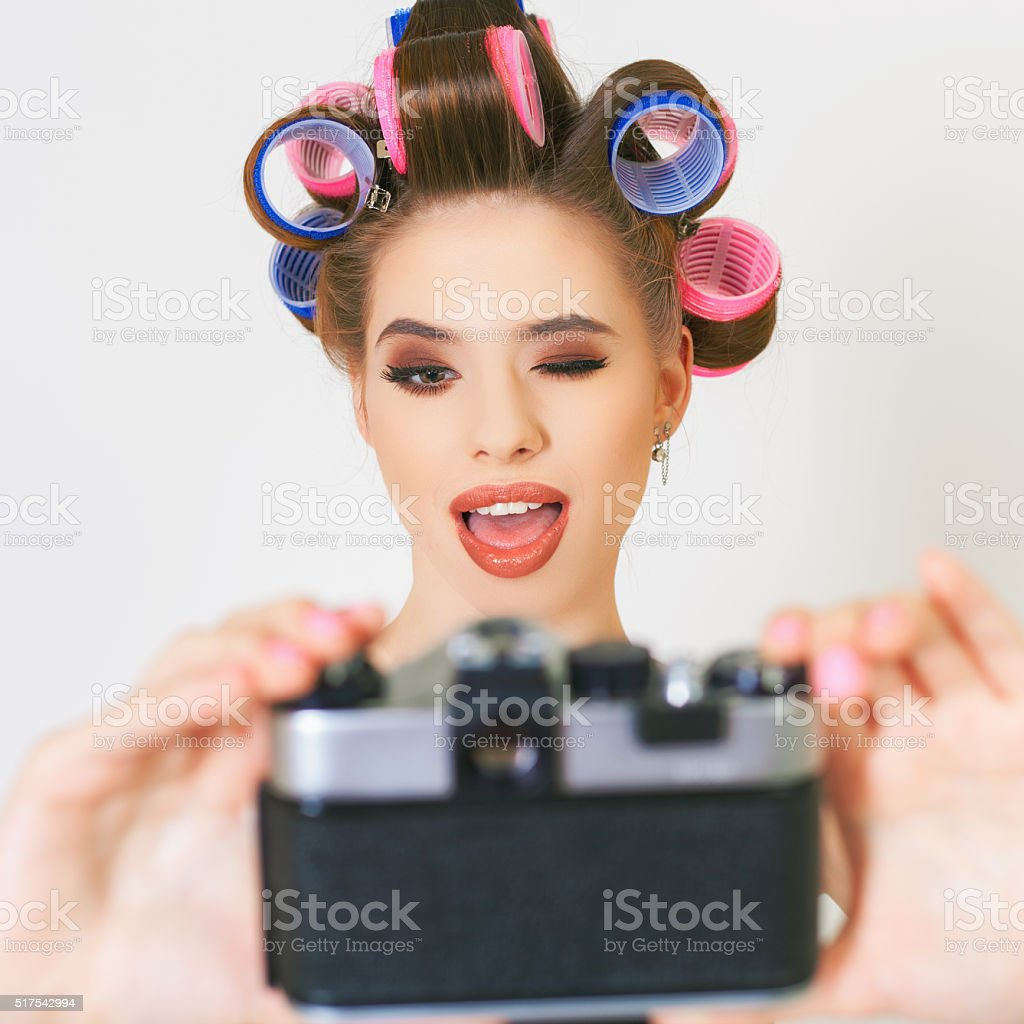 Funny girl make a foto selfie at vintage camera. stock photo