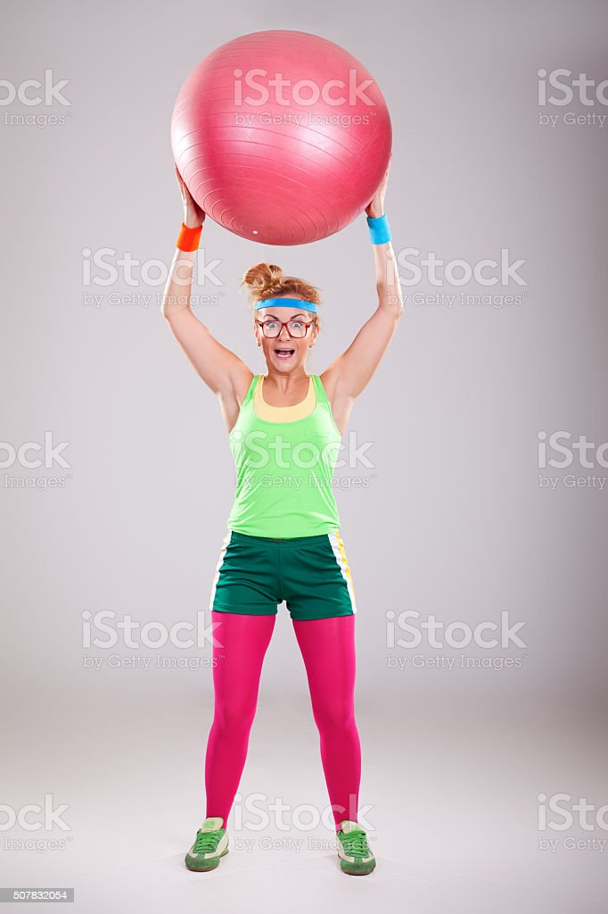 Funny girl wearing glasses doing exercises with big fitness ball stock photo