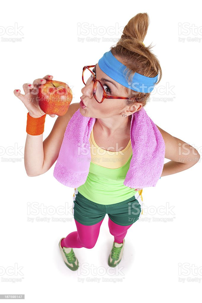 Funny girl wearing sports cloth is holdin red apple royalty-free stock photo