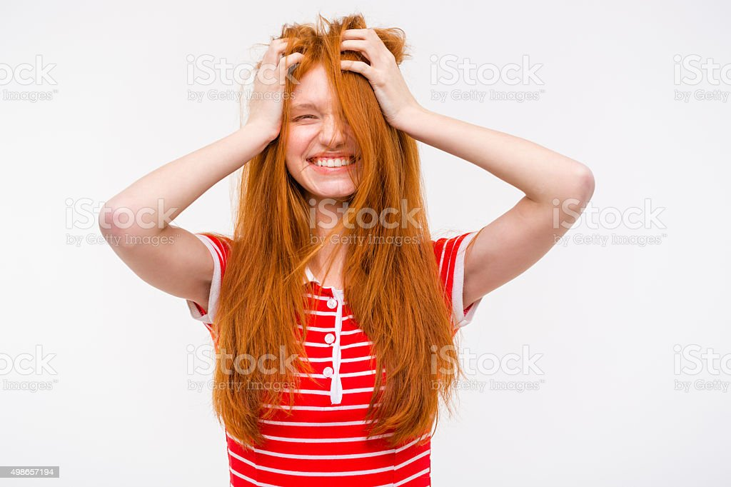 Funny girl with messy tousled hair holding hands to head stock photo