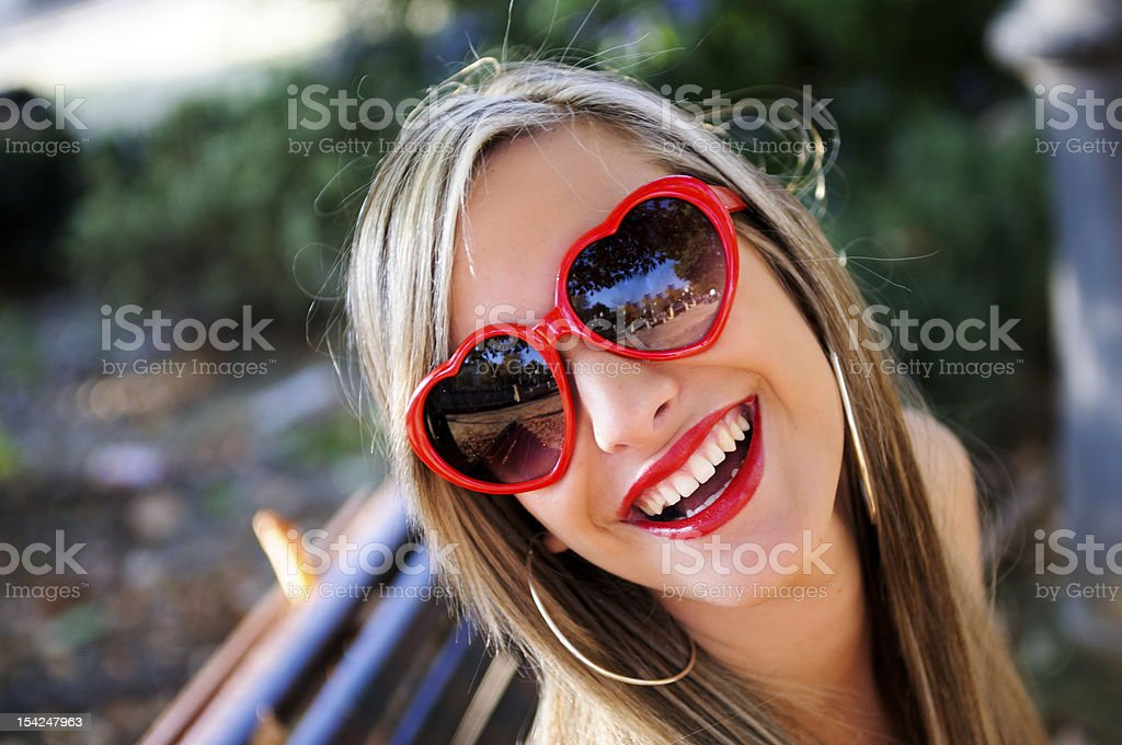 Funny girl with red heart glasses in a park royalty-free stock photo
