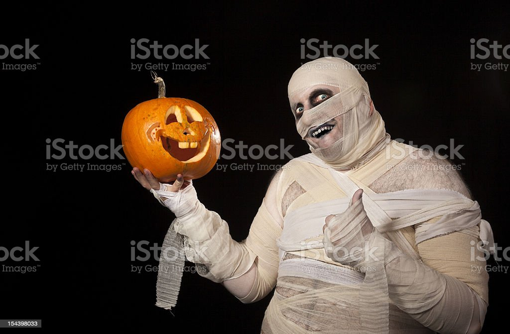 Funny halloween mummy with smiling pumpkin stock photo