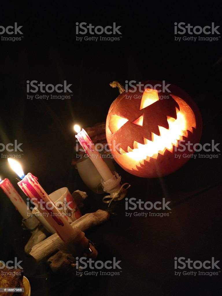 Funny Halloween pumpkin and burning candles stock photo