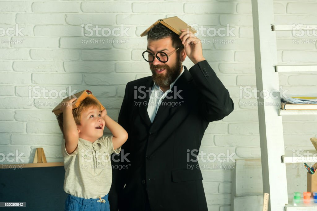 Funny happy education, home schooling with father, teacher with schoolboy reading books or playing with books on his head, mind and science, skills and knowledge, education in school or kindergarten stock photo