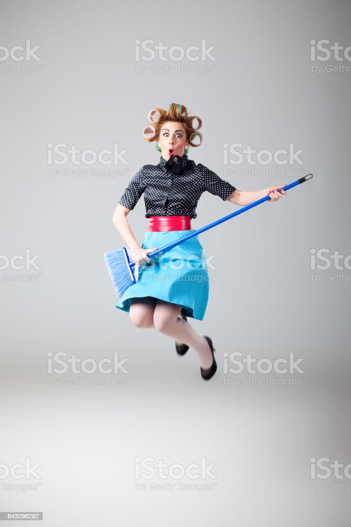 Funny housewife having fun with broom stock photo