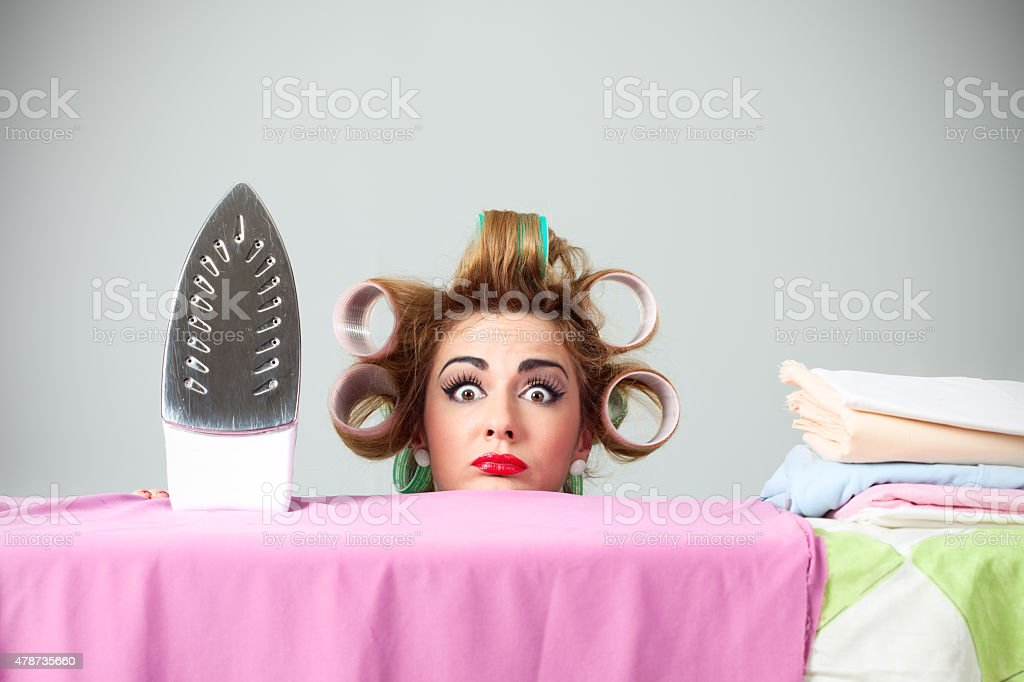 Funny housewife with curlers hiding behind ironing board stock photo