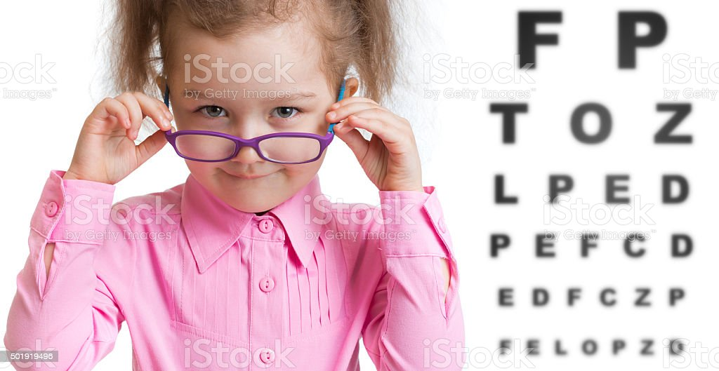Funny kid putting on spectacles in ophthalmologist office stock photo