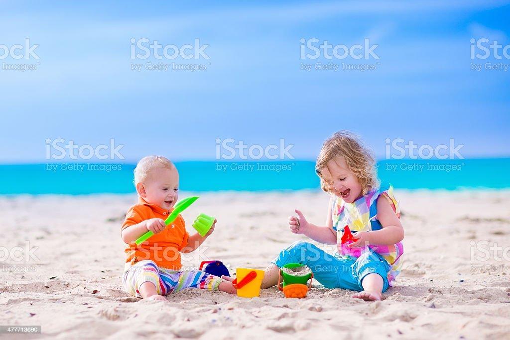 Funny kids building a sand castle on a beach stock photo