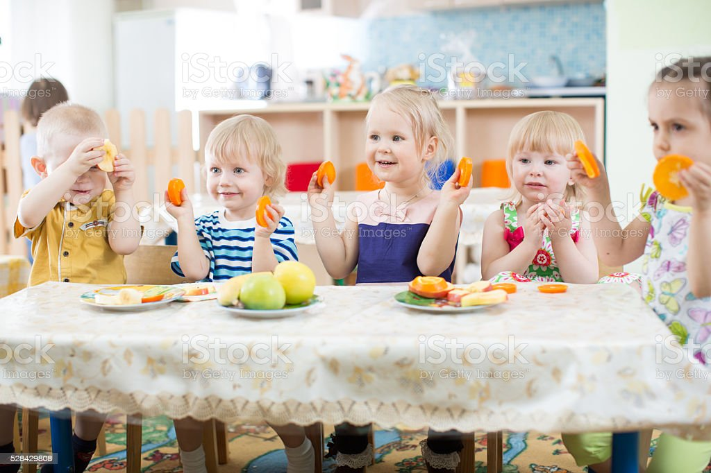 Funny kids eating fruits in kindergarten or day care centre stock photo