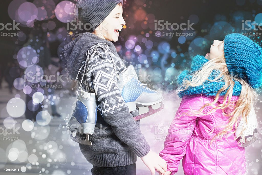 Funny kids holding ice skates shoes at ice rink outdoor stock photo