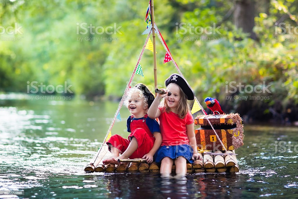 Funny kids playing pirate adventure on wooden raft stock photo