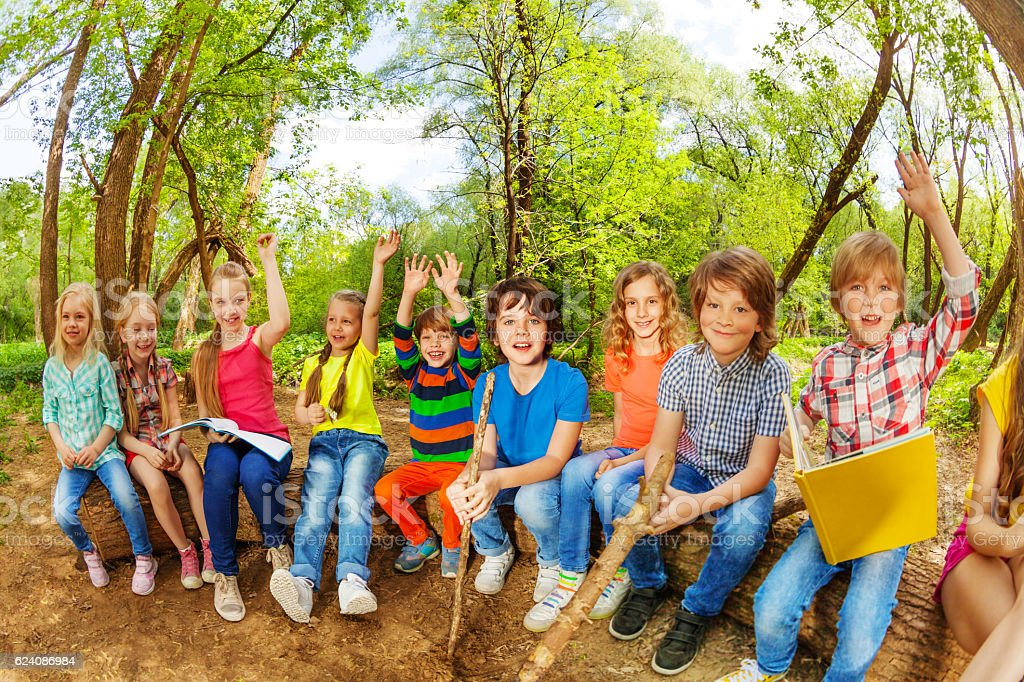 Funny kids sitting on log outdoor and reading book stock photo