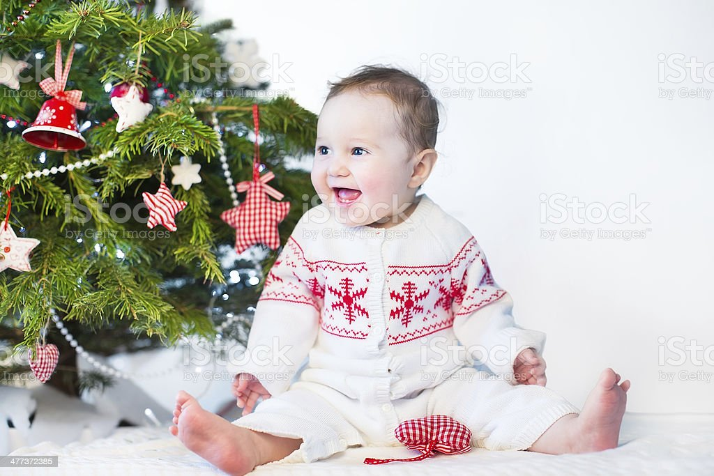 Funny laughing baby girl playing under decorated Christmas tree stock photo