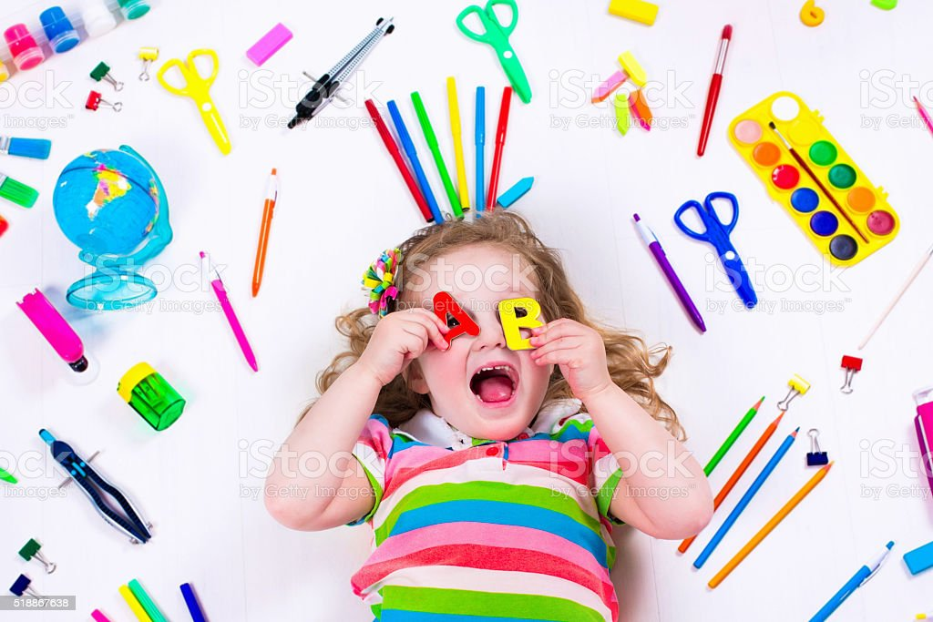 Funny littel girl with school supplies stock photo