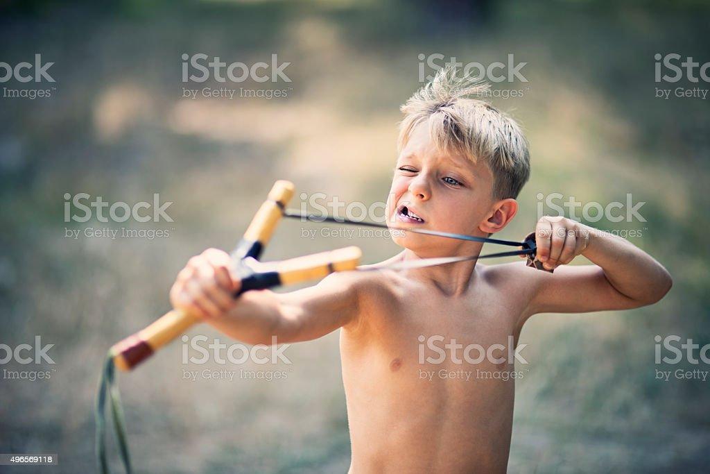 Funny little boy drawing a slingshot stock photo