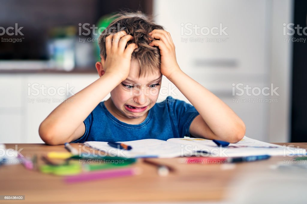 Funny little boy having problems with homework stock photo