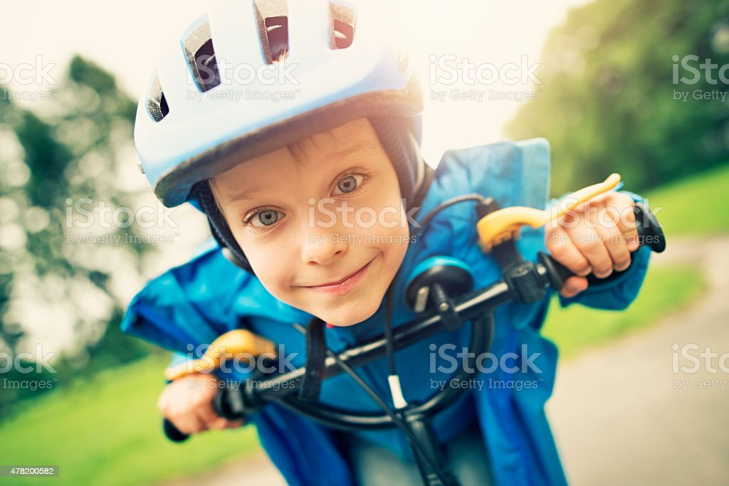 Funny little boy riding a bicycle stock photo