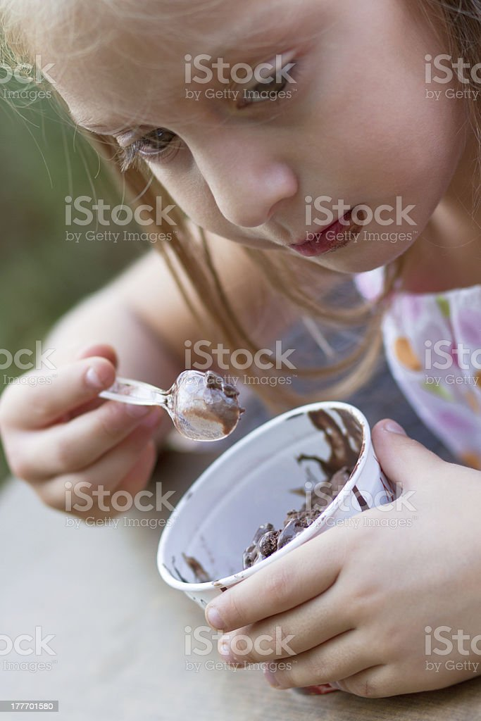 Funny little girl eats ice-cream royalty-free stock photo