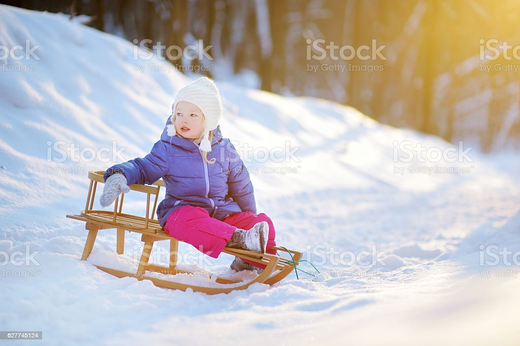 Funny little girl having fun with sleigh in winter park stock photo