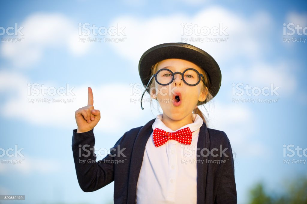 Funny little girl in glasses, bow tie and bowler hat pointing finger...