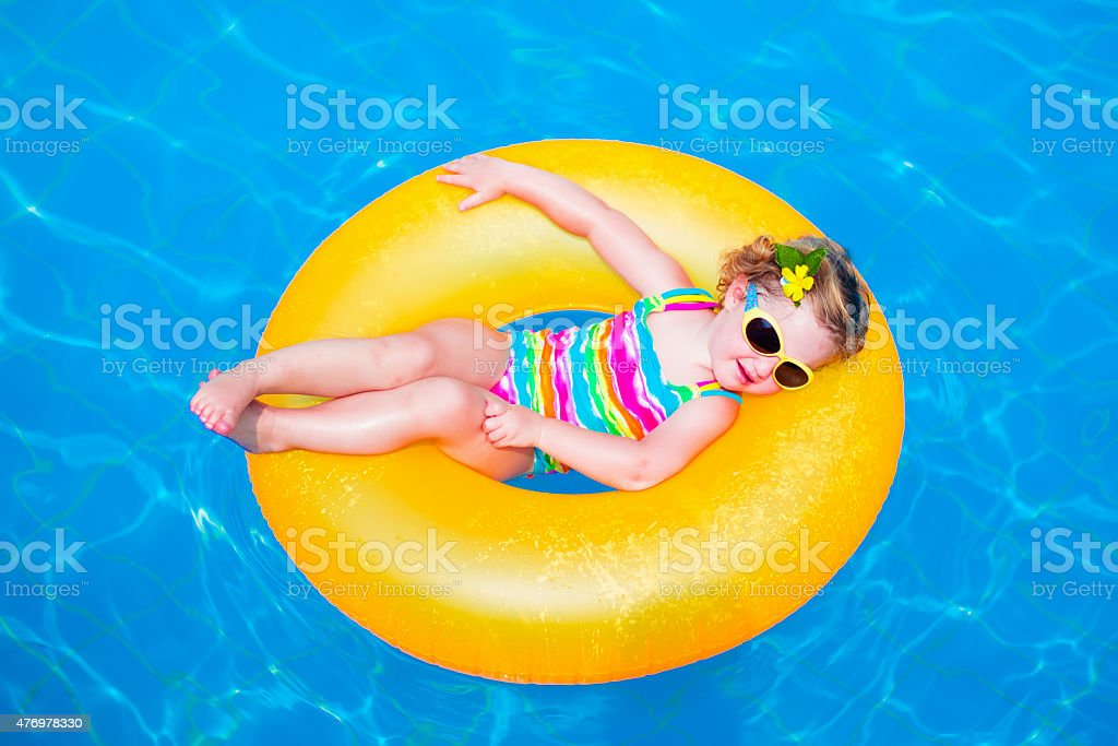 Funny little girl in swimming pool on inflatable ring stock photo