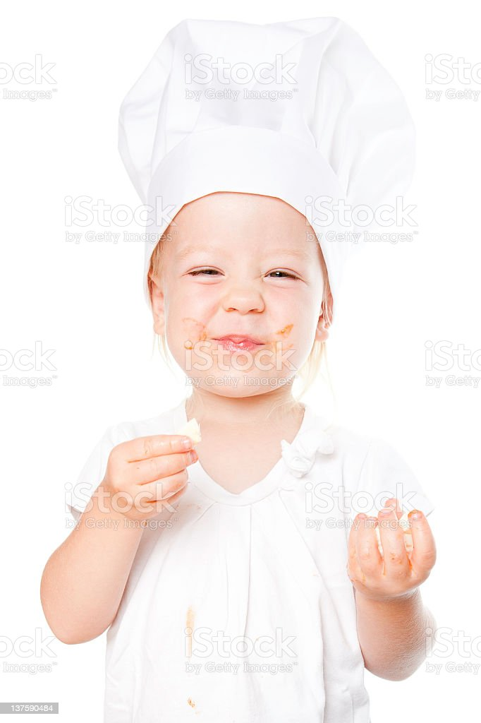Funny little girl wearing chefs hat and tasting cheese royalty-free stock photo