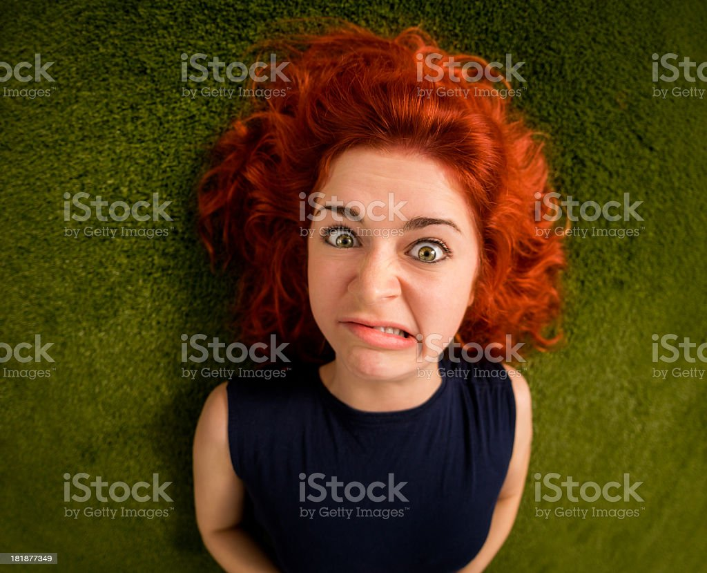 Funny looking red hair girl on grass royalty-free stock photo