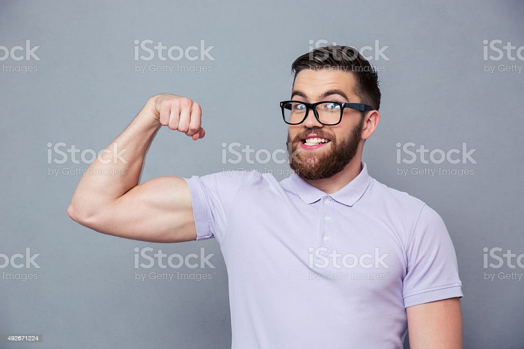 Funny man in glasses showing his muscles stock photo