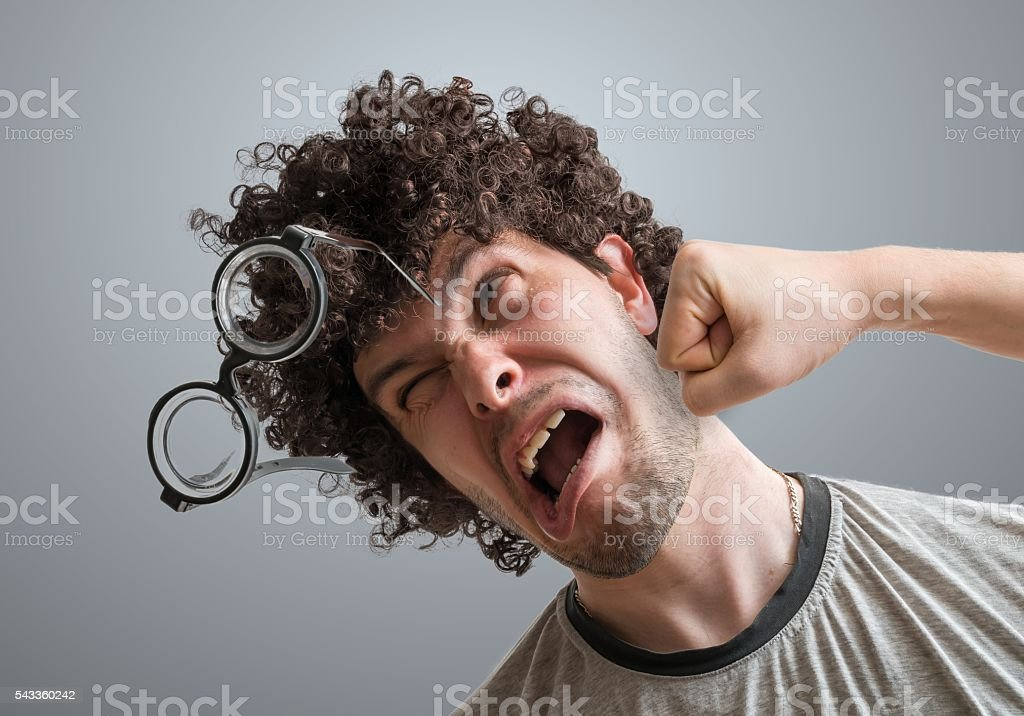 Funny man is getting punch in face with fist. stock photo