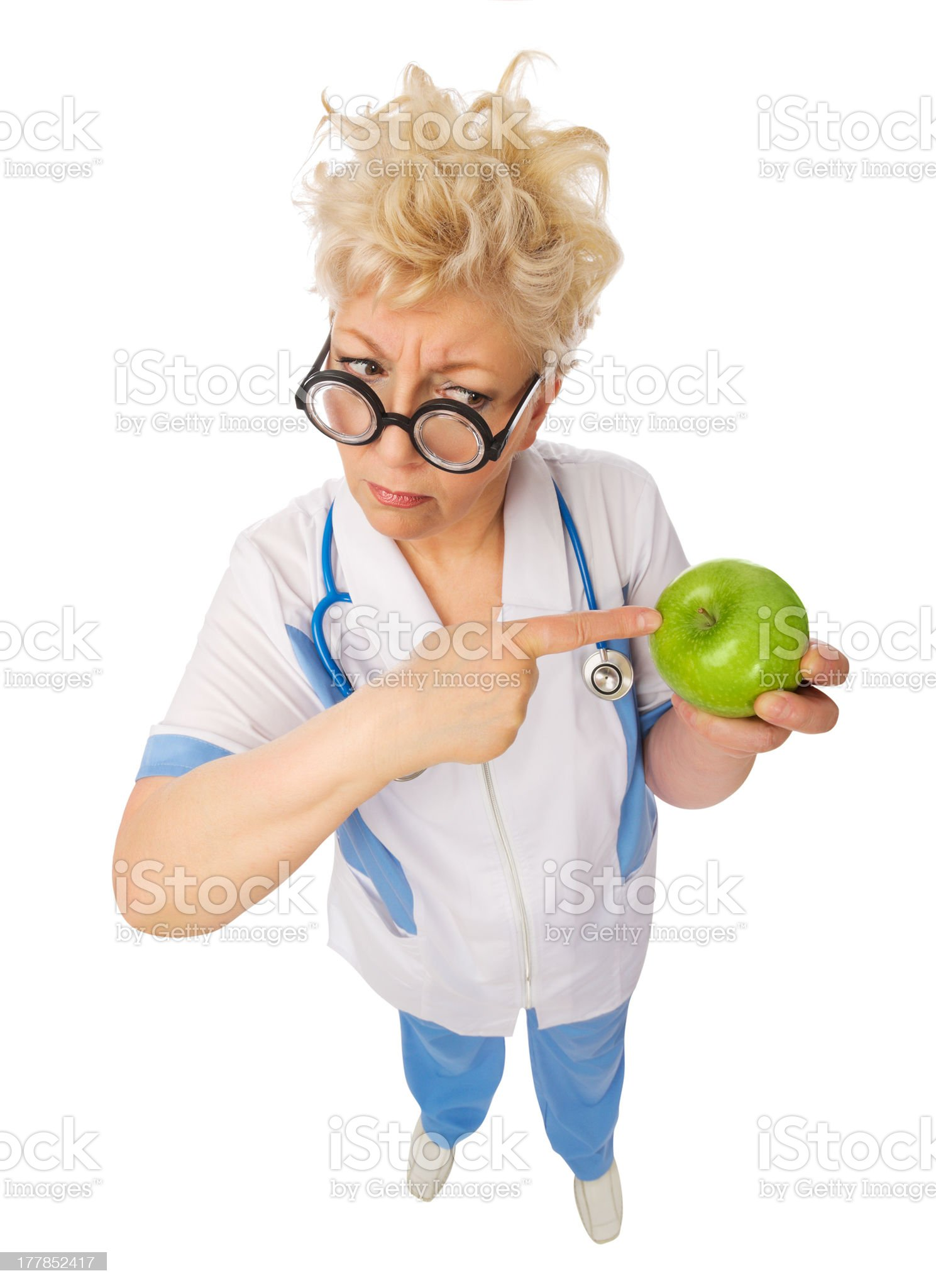 Funny mature doctor with apple royalty-free stock photo