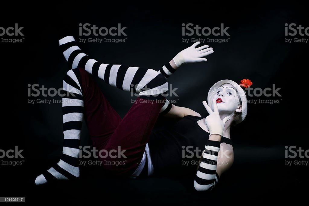 funny mime in white hat  lying on floor stock photo