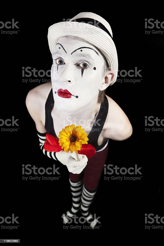 Funny mime in white hat with  bouquet of flowers royalty-free stock photo