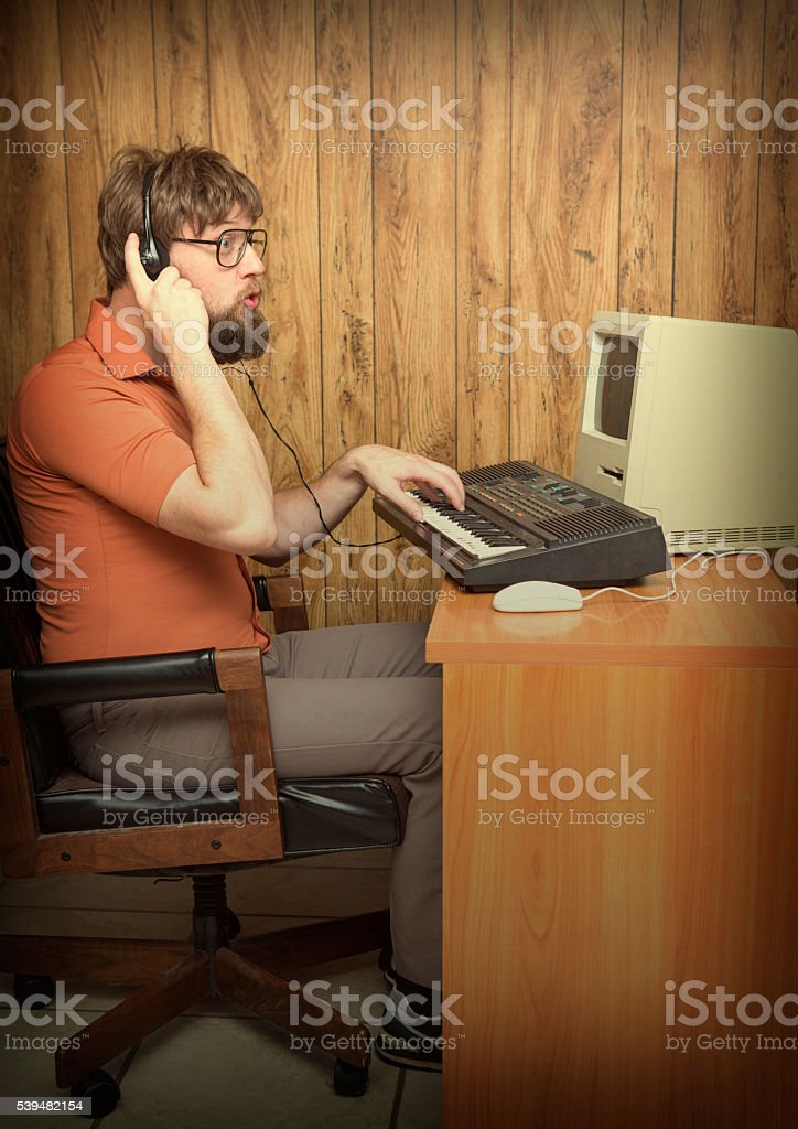Funny nerd man singing at retro synth and computer stock photo