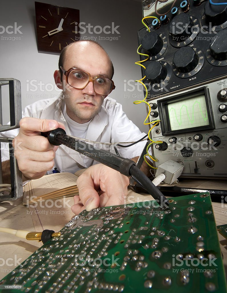 Funny nerd scientist soldering at vintage laboratory stock photo
