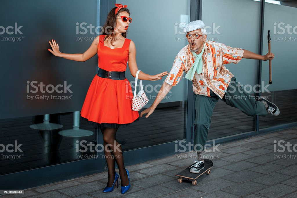 Funny old man races on a skateboard. stock photo