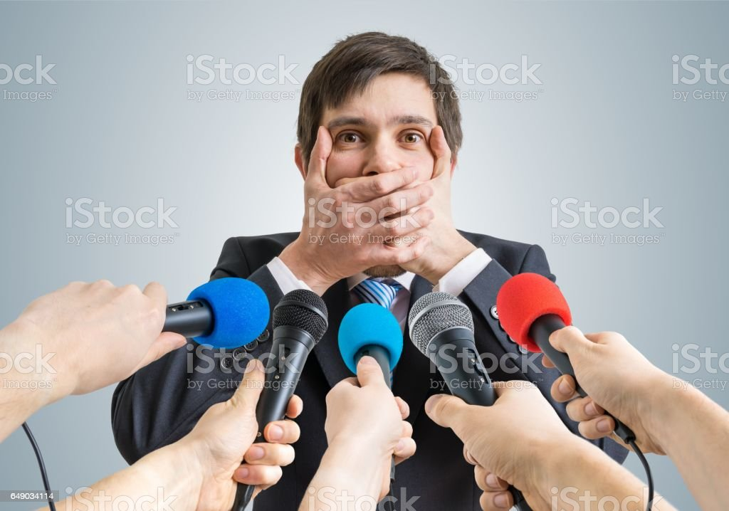 Funny politician is making no comment gesture. Many microphones in front. stock photo