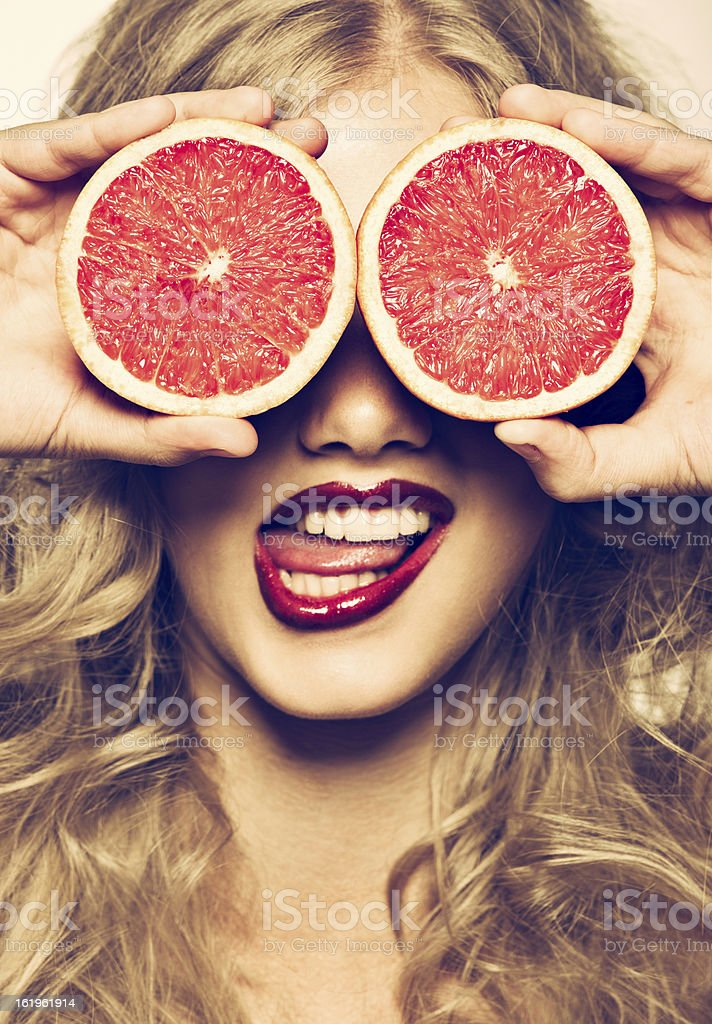 funny portrait girl holding red grapefruit infront of her face stock photo