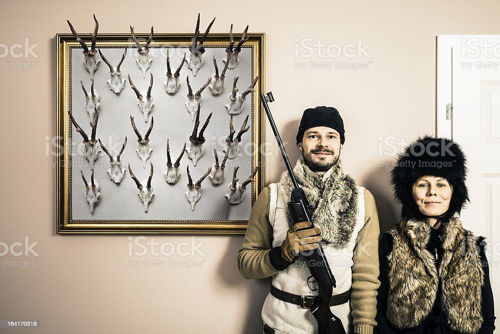 Funny portrait of content hunter and his wife with shotgun royalty-free stock photo