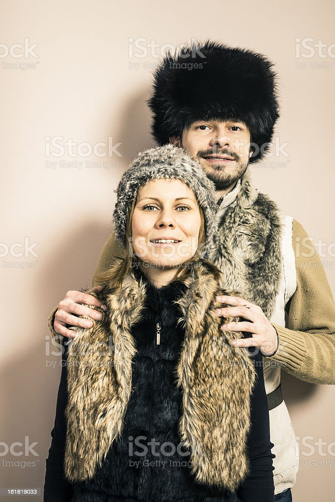 Funny portrait of hunter and his wife in animal furs stock photo