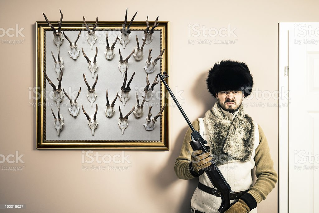Funny portrait of serious hunter man with shotgun and antlers stock photo