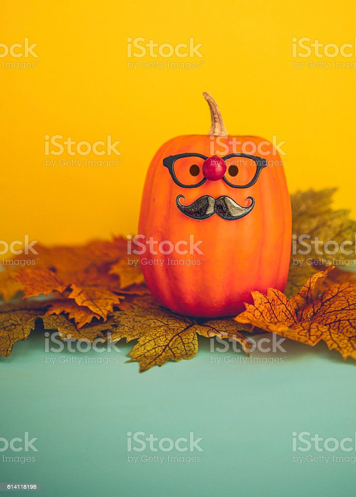 Funny pumpkin character wearing mustache and red nose for Halloween stock photo