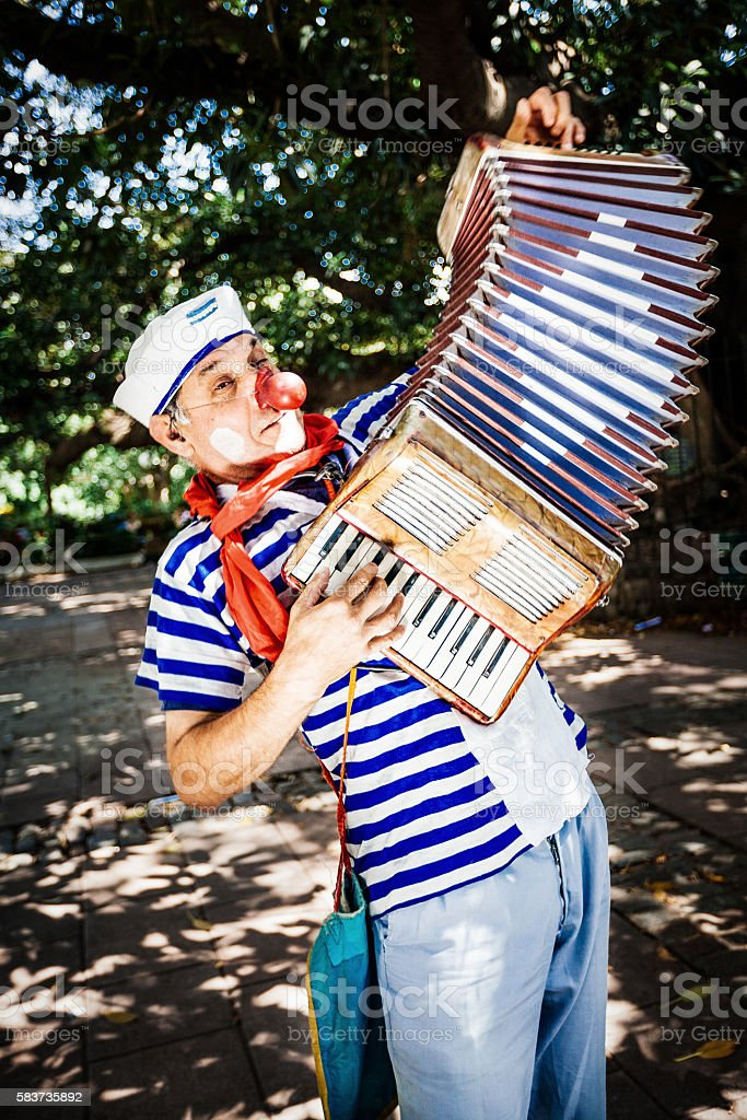 Funny sailor clown playing on piano accordion stock photo