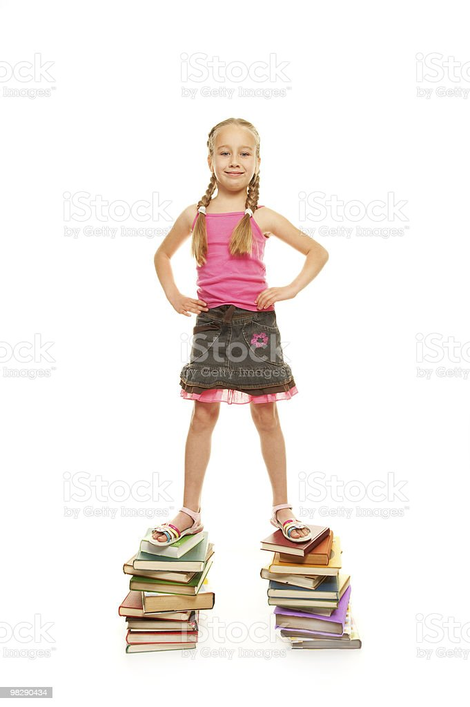 Funny schoolgirl standing on the books royalty-free stock photo