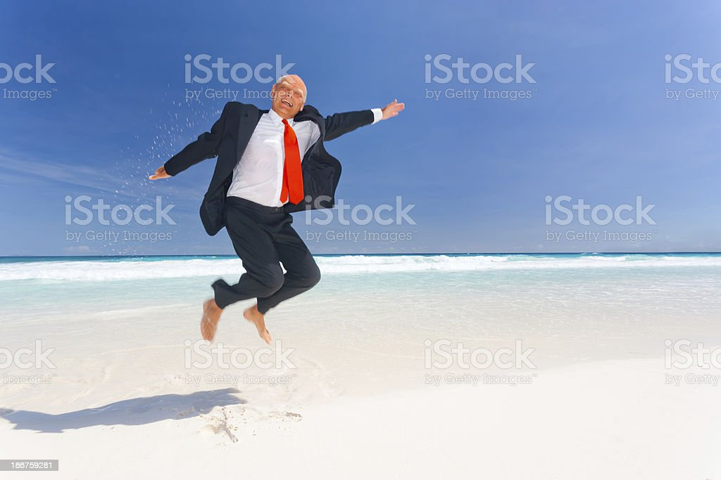 funny senior businessman jumping on the beach royalty-free stock photo