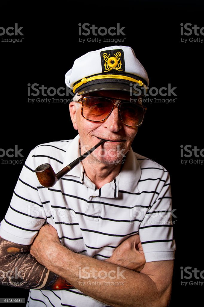 Funny senior sailor man with cigar and tattoo on arm stock photo