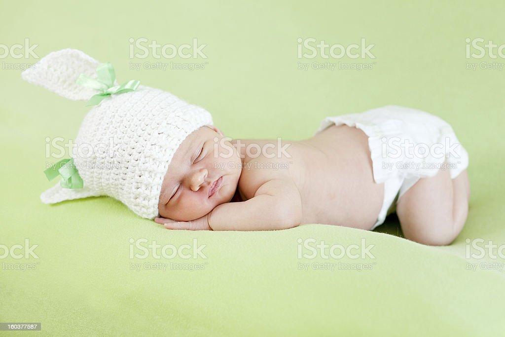 Funny sleeping newborn child. Bunny cap on head of girl. stock photo