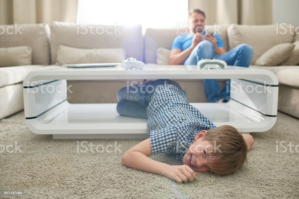 Funny son under coffee table stock photo