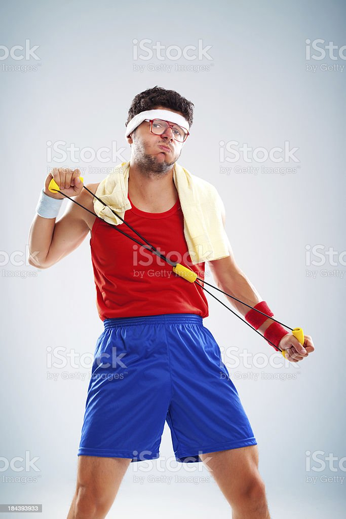 Funny sportsman doing exercises with resistance band stock photo